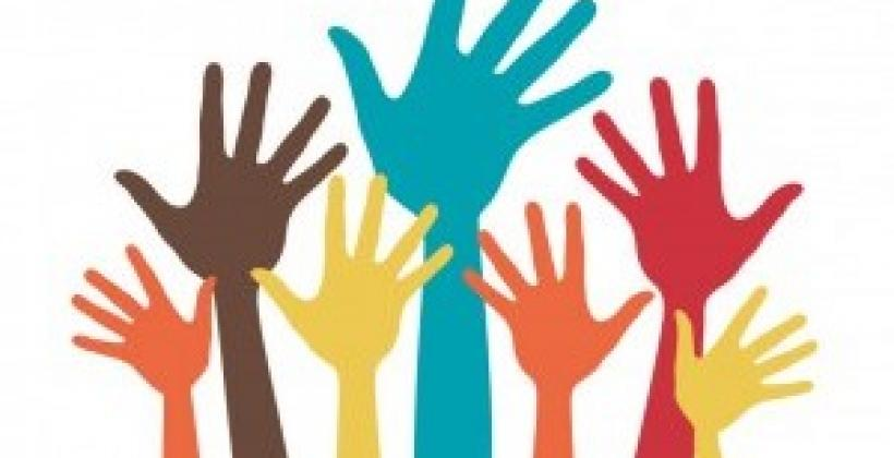 Many coloured hands raised